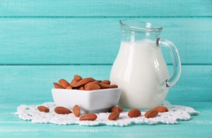 Almond milk in jug with almonds in bowl, on color wooden background